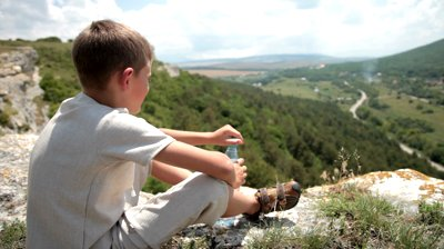 stock-footage-young-boy-drinking-purified-water-in-the-mountains
