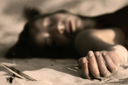 woman playing dead, lying in the sand