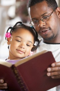 Father and Daughter Reading Bible --- Image by © Ocean/Corbis