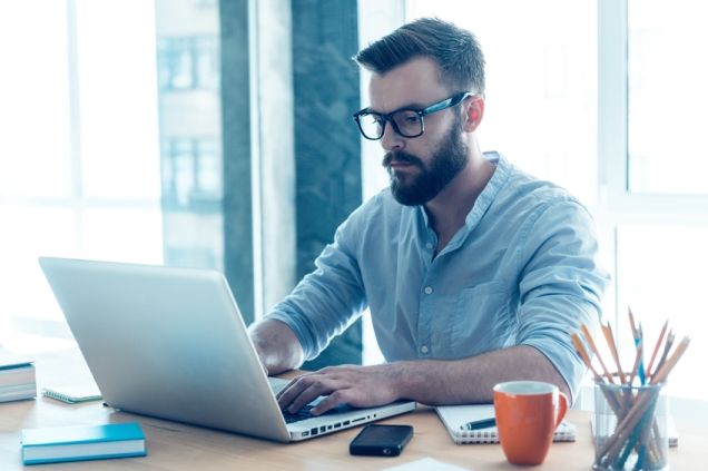 Concentrated young beard man working on laptop while sitting at his working place in office