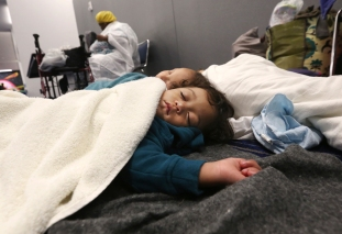 Robert Salgado, 2, sleeps on the floor at the George R. Brown Convention Center that has been set up as a shelter for evacuees escaping the floodwaters from Tropical Storm Harvey in Houston, Texas, Tuesday, Aug. 29, 2017. (AP Photo/LM Otero)