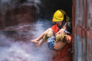 bombero-sosteniendo-nino-nino-salvarlo-fuego-humo_42044-4154