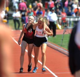 Megan Vogel, high school runner, helps her rival cross the finish line