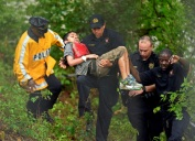 "A young boy is carried by a rescue worker as Dallas Police and Fire Department members take part in a high water rescue near Glen Oaks and Brook Valley in Dallas, Texas. on Thursday, May 8, 2014. According to Dallas police, a group of students who were skipping school were trapped in a drainage tunnel along a tributary of Woody Branch. Dallas Fire-Rescue spokesman Jason Evans said the five teenagers rescued from the water were skipping school. All five teens were taken to Children's Medical Center and were ""awake and alert."" (AP Photo/The Dallas Morning News, Michael Ainsworth) MANDATORY CREDIT; MAGS OUT; TV OUT; INTERNET USE BY AP MEMBERS ONLY; NO SALES"