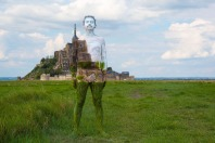 ***MANDATORY BYLINE*** PIC BY TRINA MERRY/CATERS NEWS (PICTURED: A man blends into the stunning view of Mont St Michel in Normandy, France) - A New York artist has used body paint to perfectly camouflage her subjects into a variety of famous landmarks. Trina Merry, who specialises in bodypainting, line her subjects up and photographed them as they appeared to blend right into the scenery around them. The backdrops to her eye-catching art include the White House, Freedom Tower, Grand Central Station, the Golden Gate Bridge, and even Irelands Giants Causeway. By painting her subjects into a modern background, Trina is putting a modern twist on the oldest art form known to man. SEE CATERS COPY