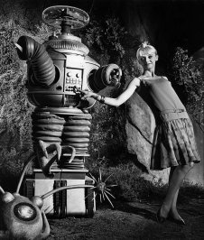 "1965: Model playing with Robby the Robot. Model is wearing bouncy dress designed by Sue Webb for Pixie of California. This photo was published in the Nov. 4, 1965 Los Angeles Times. Photo was taken on set of ""Lost in Space."""
