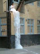 Peformanc artist Sachiko Abe sits atop a watery (cut paper) gown