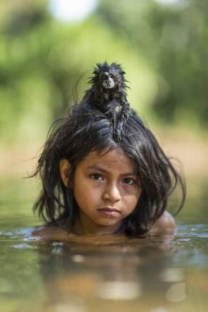 Matsigenka girl swimming with her pet Tamarin (CharlesHamiltonJamesArt.com)